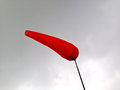 Fire red airsock gray steel sky before storm with Stock Image
