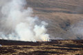 Fire and smoke on burning moorland vegetation a hillside near garsdale in north yorkshire england Stock Image