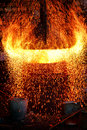 Fire sparks and blazing flames in blast furnace intense splashing sparkling out of an antique cast iron making smelting hot with Stock Photos