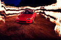 Fire wall behind red sports car Royalty Free Stock Photo