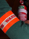 Fire warden with a reflective high visibility identification patch holding a fire extinguisher Royalty Free Stock Photo