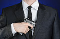 Firearms and security topic a man in a black suit holding a gun on a dark blue background in studio isolated Stock Photo