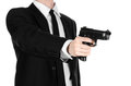 Firearms and security topic a man in a black suit holding a gun on an isolated white background in studio Stock Photo