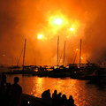 Fireball fireworks scenery at harbor orange explosion in the night sky over the with the silhouettes of boats anchoring and people Stock Images