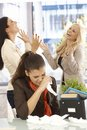 Fired employee crying at desk female colleagues celebrating the background Royalty Free Stock Image