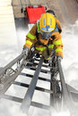 Firefighter ascends upon a one hundred foot ladder Royalty Free Stock Image