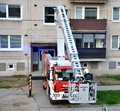 Firefighter begin to uprise into telescopic boom basket of fire truck, block of flats in background Royalty Free Stock Photo