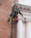 Firefighter climbing with ropes and climbing equipment on an old Royalty Free Stock Photo