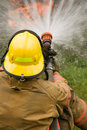 Firefighter dousing house fire Royalty Free Stock Photos