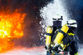 Firefighter firemen extinguishing a large blaze they are standing with protective wear in front of wall of fire Stock Photos