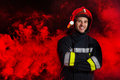 Firefighter posing with arms crossed smiling fireman in red helmet three quarter length studio shot on black background red smoke Stock Images
