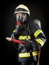 Firefighter in protective gear wearing suit helmet and mask Stock Photos