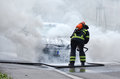 Firefighter is putting out a burning car motor vehicle been put by fireman in protective clothing Stock Photos