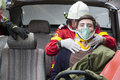 Firefighter rescuing victim holding wounded young man in car accident photo taken during an exercise Stock Photo