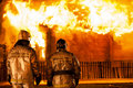 Firefighters at burning fire flame on wooden house roof arson or nature disaster Stock Photo