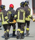 Firefighters carry a fellow firefighter four brave with the medical stretcher Royalty Free Stock Image