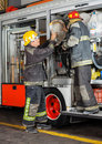 Firefighters removing hose from truck full length of male in fire station Stock Images