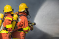 2 firefighters spraying water in fire fighting with dark smoke b Royalty Free Stock Photo