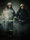 Firefighters two with axes in a smoke Stock Photography