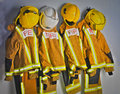 Firefighters uniforms with helmets in locker room Stock Photos