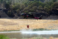 Firefighting helicopter refills water bucket a its in a pond while hovering above Stock Photo