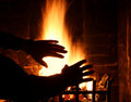 Firelight hands warming by white hot log fire in a huge old fireplace Royalty Free Stock Photo