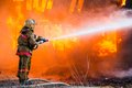 Fireman extinguishes a fire in an old wooden house Stock Photo