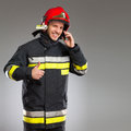 Fireman holding smart phone and showing thumb up smiling with cell looking at camera three quarter studio shot on gray background Stock Image