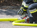 Fireman at work operating the valve of a firehose Royalty Free Stock Image