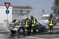 Firemen extinguishing a car fire italian firefighters on parked in gas station piacenza northern italy Stock Image