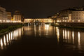 Firenze ponte vecchio old bridge by night with reflection in the is a medieval stone closed spandrel segmental arch over the arno Stock Photos