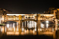 Firenze ponte vecchio old bridge by night with reflections in the is a medieval stone closed spandrel segmental arch over the arno Royalty Free Stock Photo
