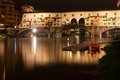 Firenze ponte vecchio old bridge by night view from the rive is a medieval stone closed spandrel segmental arch over arno river in Stock Images