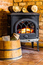Fireplace with fire flame and firewood in barrel interior heating winter at home closeup of orange the Royalty Free Stock Photography