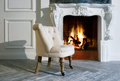 Fireplace white armchair by the Stock Photo