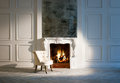 Fireplace white armchair by the Royalty Free Stock Image