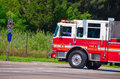Firetruck driving fast with flashing lights red and white down the road and sirens on Royalty Free Stock Photos