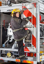 Firewoman climbing truck at fire station rear view portrait of young Stock Images