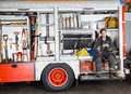 Firewoman holding coffee mug in truck full length of while sitting at fire station Stock Photography