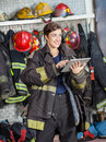 Firewoman looking away while using digital tablet smiling at fire station Royalty Free Stock Image