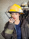 Firewoman using walkie talkie at fire station portrait of confident Stock Photo