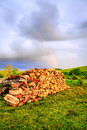 Firewood pile of on a backyard with rainbow in the background Stock Images