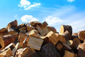 Firewood pile and blue sky with cloud closeup Royalty Free Stock Image