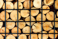 Firewood stacked on the woodpile in iron cage, background. Royalty Free Stock Photo
