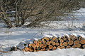 Firewood to be split stacked under the snow image of a stack of waiting Stock Photo