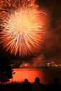 Fireworks over a city yellow and red exploding they are reflecting in the water and two spectators are enjoying the show Royalty Free Stock Images