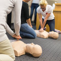 First aid cpr seminar a group of adult education students practitcing chest compressioon on a dummy Royalty Free Stock Image