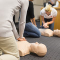 First aid cpr seminar a group of adult education students practitcing chest compressioon on a dummy Royalty Free Stock Photos