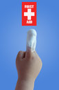 First aid finger of a children with on a blue bottom Royalty Free Stock Images