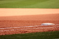 First base featured in empty baseball field is showing infield dirt and outfield grass Royalty Free Stock Photos
